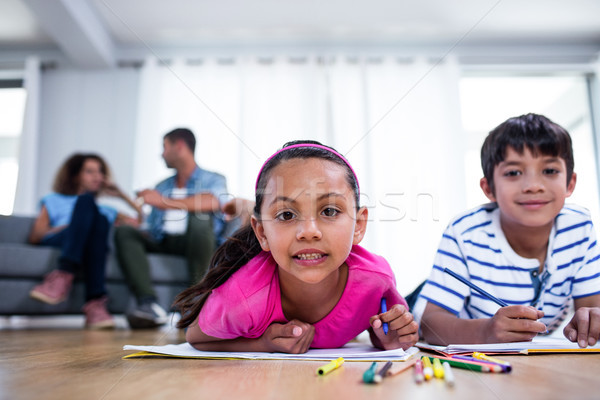 Portrait of brother and sister lying on floor and drawing Stock photo © wavebreak_media