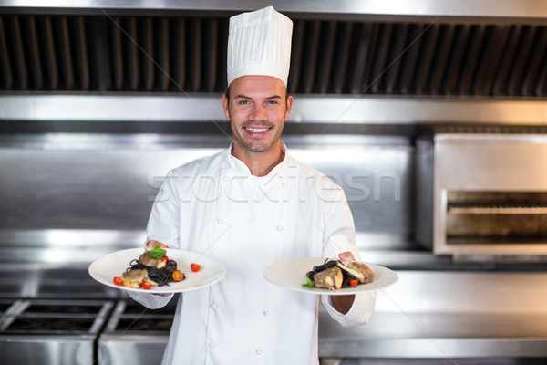 Portrait of smiling chef holding plates in kitchen Stock photo © wavebreak_media