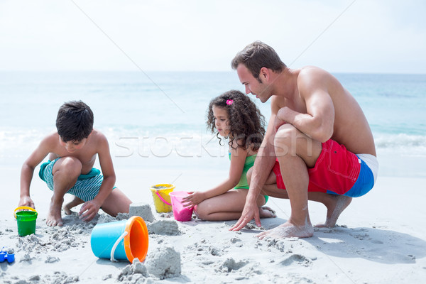 Father helping children building sand castle at beach  Stock photo © wavebreak_media