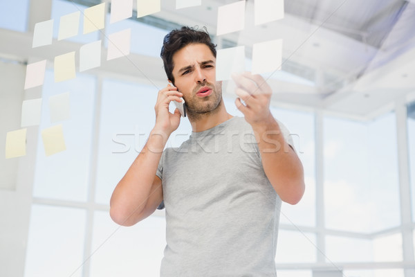 Man looking at a sticky notes while talking on phone Stock photo © wavebreak_media