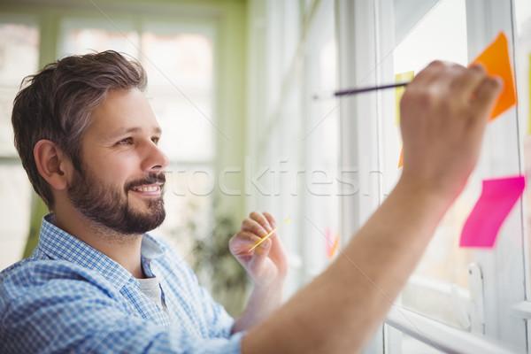 Mosolyog üzletember ír tapadó jegyzetek iroda Stock fotó © wavebreak_media