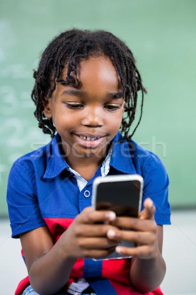 Smiling boy using mobile phone in classroom Stock photo © wavebreak_media