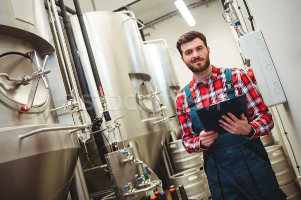 Portrait of manufacturer holding writing pad in brewery Stock photo © wavebreak_media