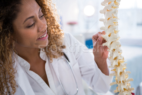 Smiling physiotherapist looking at spine model Stock photo © wavebreak_media