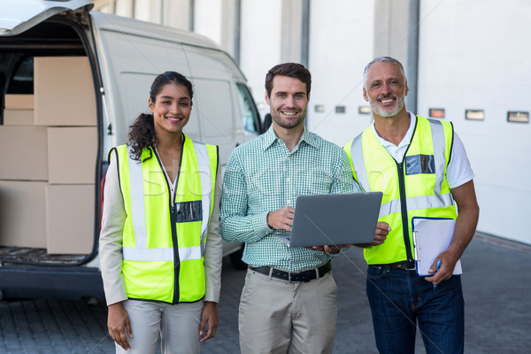 Manager and warehouse workers standing with laptop and clipboard Stock photo © wavebreak_media