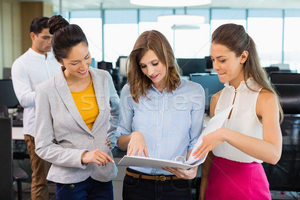 Business colleagues discussing over clipboard at desk in office Stock photo © wavebreak_media