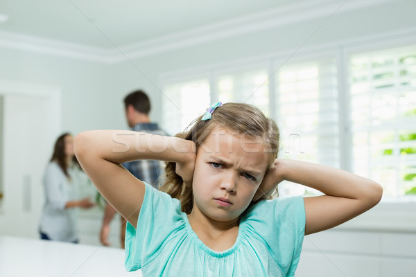 Girl covers her ears with her hands while parents arguing in background Stock photo © wavebreak_media