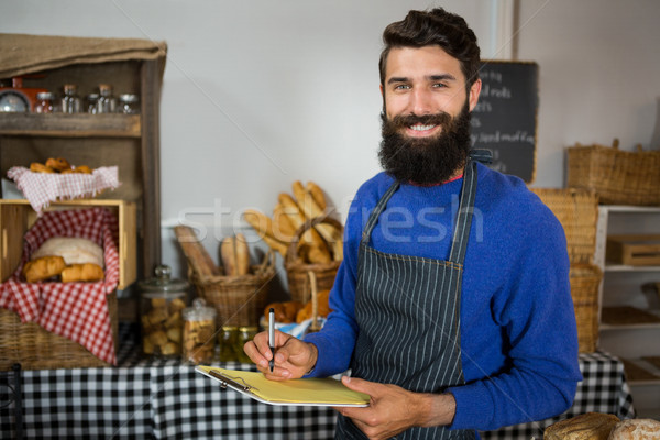 Mosolyog férfi személyzet ír vágólap pult Stock fotó © wavebreak_media
