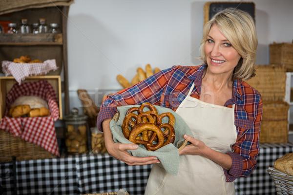 Smiling female staff holding wicker basket of pretzel bread at counter Stock photo © wavebreak_media