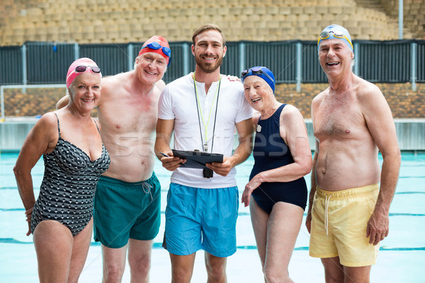 Cheerful seniors people with instructor standing at poolside Stock photo © wavebreak_media