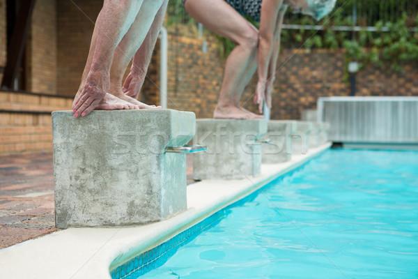 Stock photo: Two senior women preparing to dive in pool