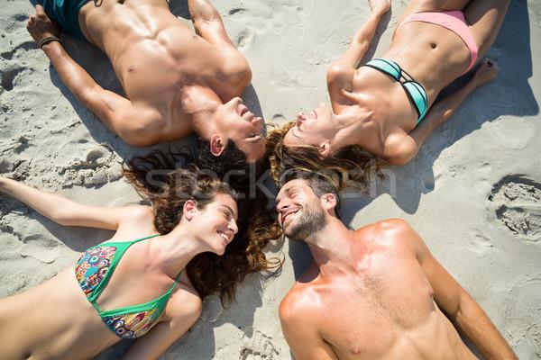 счастливым друзей солнечные ванны пляж женщину улыбаясь Сток-фото © wavebreak_media