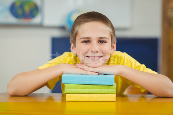 Smiling pupil leaning on pile of books in a classroom Stock photo © wavebreak_media