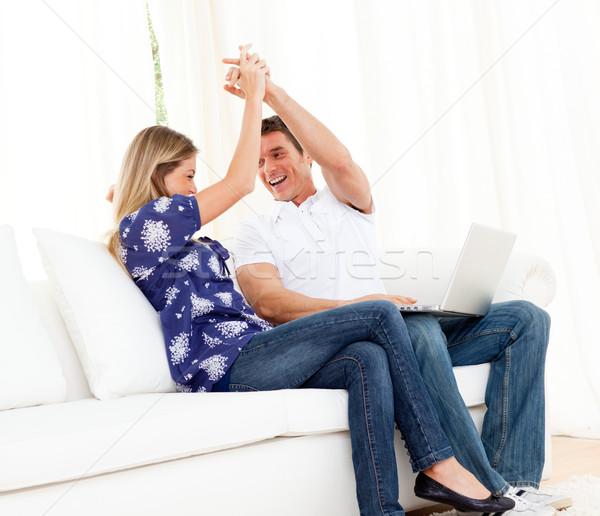 Lively couple using a laptop sitting on sofa Stock photo © wavebreak_media