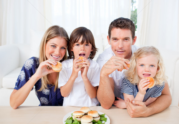 Enthusiastic family eating burgers in the living room Stock photo © wavebreak_media