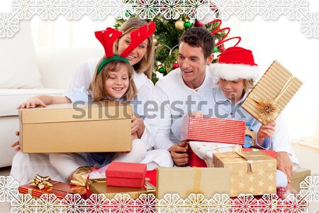 Portrait of a happy family unpacking Christmas presents Stock photo © wavebreak_media