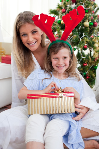Smiling mother and her daughter unpacking Christmas gifts Stock photo © wavebreak_media