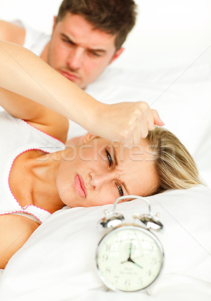 Attractive man and angry woman in bed looking at the alarm clock going off Stock photo © wavebreak_media