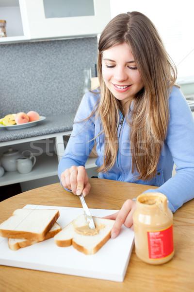 Glowing woman woman eating peanut butter in a kitchen Stock photo © wavebreak_media