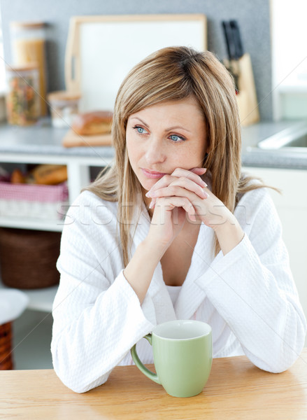 Thinking woman with a cup in kitchen Stock photo © wavebreak_media