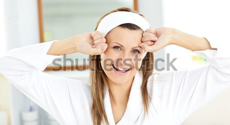 Beautiful woman stretching while standing in the bathroom wearing a bath robe Stock photo © wavebreak_media