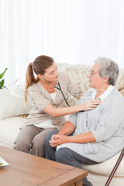 Nurse taking the heartbeat of her patient at home Stock photo © wavebreak_media