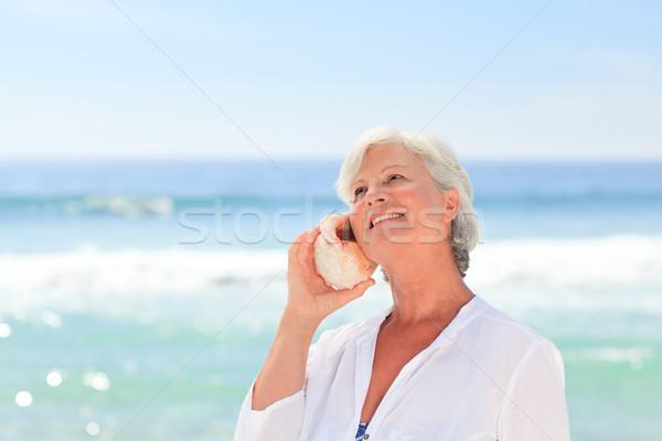 Reife Frau hören Shell Frau Strand Mädchen Stock foto © wavebreak_media