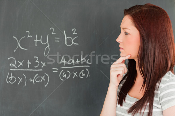 Pensive cute woman trying to solve an equation in a classroom Stock photo © wavebreak_media