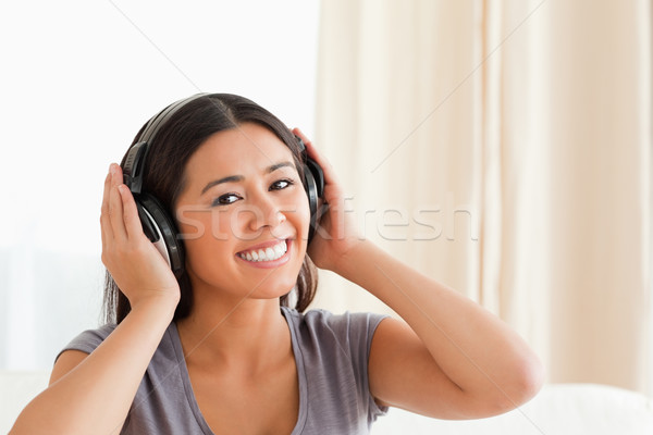 close up of a charming woman with earphones looking into camera in livingroom Stock photo © wavebreak_media