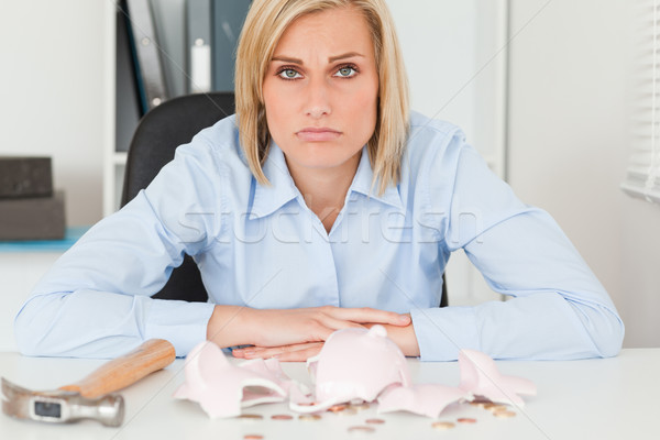 Sad woman sitting in her office in front of an shattered piggy bank with less in than expected Stock photo © wavebreak_media