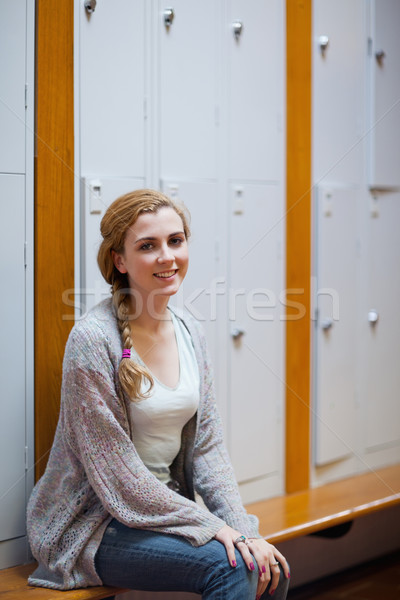 Portrait of a smiling student sitting on a bench in a corridor Stock photo © wavebreak_media