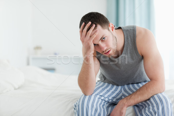 Stock photo: Tired man sitting on his bed while looking at the camera