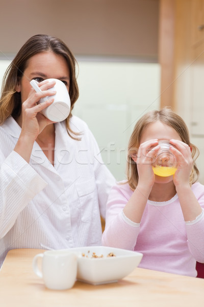 Portrait of a charming mother and her daughter having breakfast in a kitchen Stock photo © wavebreak_media