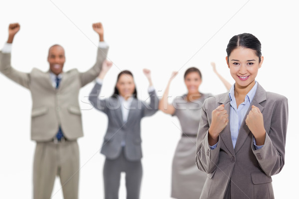 Close-up of a businesswoman smiling and clenching her fists with enthusiastic co-workers in the back Stock photo © wavebreak_media