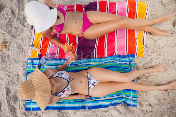 Overhead view of two young women tanning in the sun while wearing swimsuits Stock photo © wavebreak_media