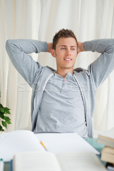 Student stretching while looking away in front of his homework Stock photo © wavebreak_media