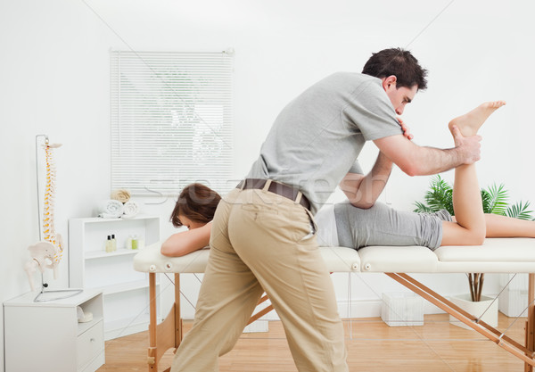 Brunette woman being stretched by a physiotherapist in a room Stock photo © wavebreak_media