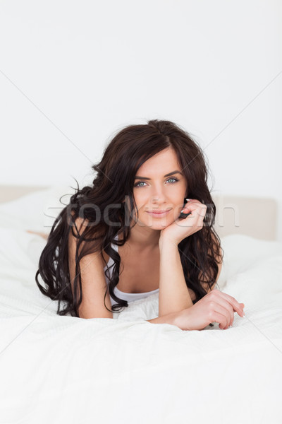 Smiling woman lying on her bed with her hand on her chin indoors Stock photo © wavebreak_media