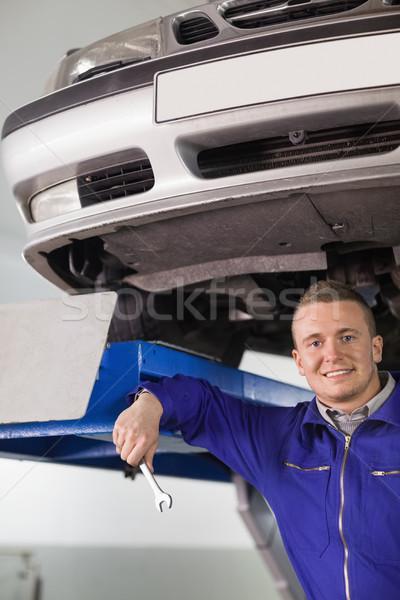 Souriant mécanicien clé au-dessous voiture Photo stock © wavebreak_media