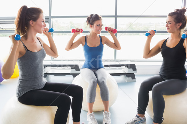 Stock photo: Three women on exercise balls lifting weights in gym