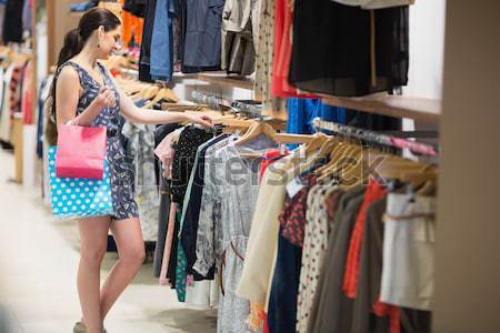 Woman standing by clothes rail in boutique Stock photo © wavebreak_media