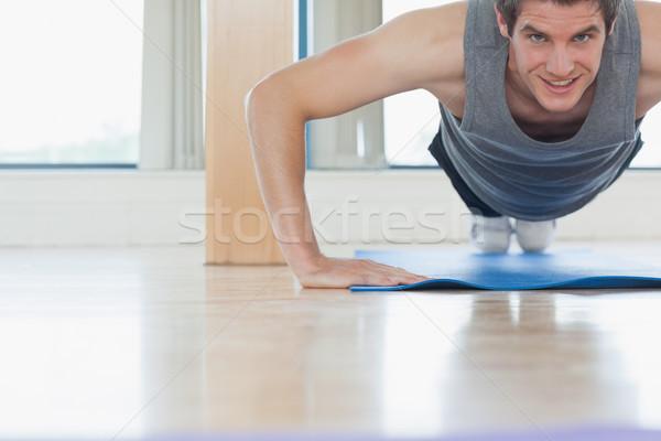 Hombre flexiones gimnasio sonriendo sonrisa deporte Foto stock © wavebreak_media