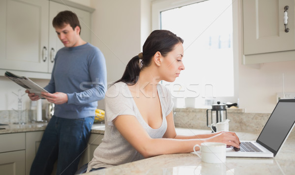Two people in the kitchen who are using the laptop and reading a magazine Stock photo © wavebreak_media
