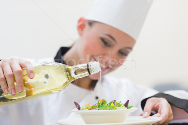 Smiling woman chef dressing a salad in the kitchen Stock photo © wavebreak_media