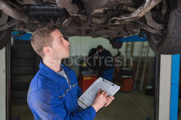 Stock photo: Mechanic under car preparing checklist