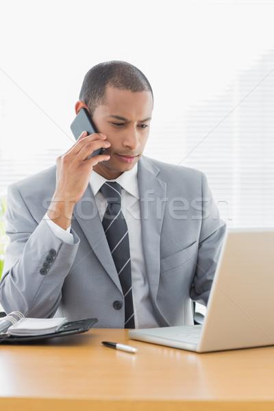 Stockfoto: Zakenman · met · behulp · van · laptop · mobieltje · kantoor · geconcentreerde · jonge