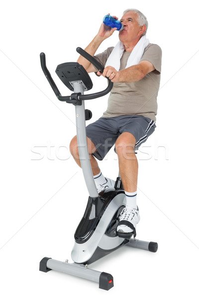 Idős férfi ivóvíz mozdulatlan bicikli teljes alakos Stock fotó © wavebreak_media