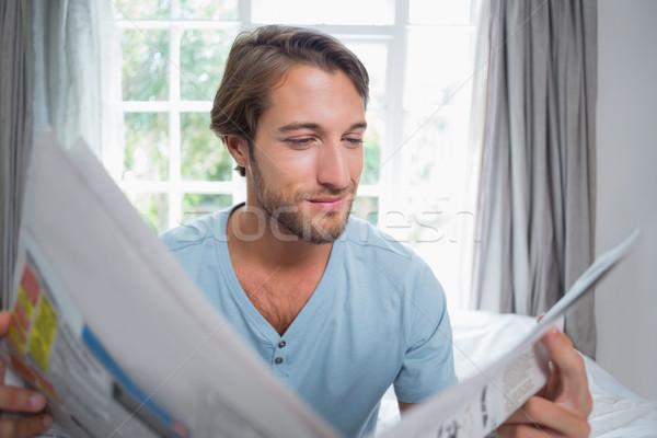 Knappe man vergadering bed lezing krant home Stockfoto © wavebreak_media