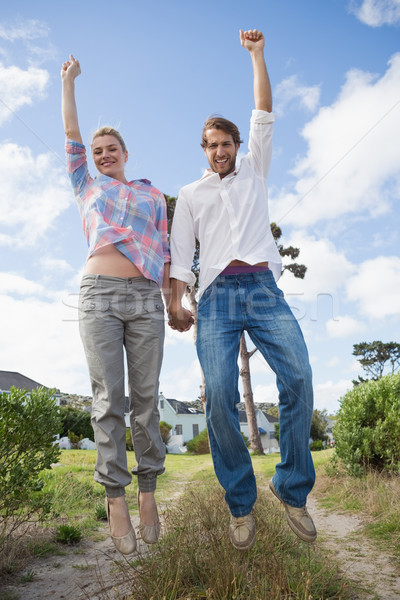 Smiling couple leaping outside together in their garden Stock photo © wavebreak_media
