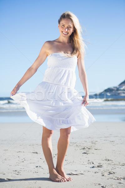 Femeie rochie de culoare alba zâmbitor aparat foto plajă luminos Imagine de stoc © wavebreak_media